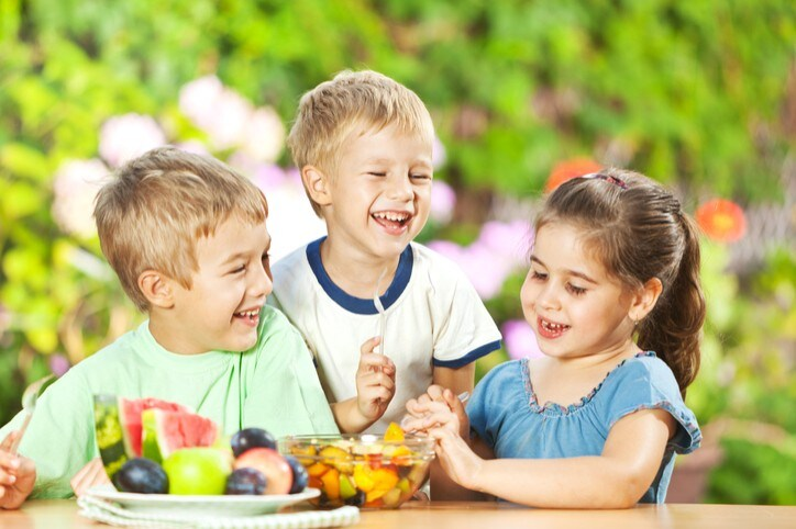Group of small children having healthy snack, eating fresh fruit salad outdoors.